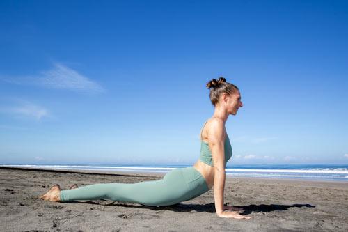 Caroline practicing yoga on the beach